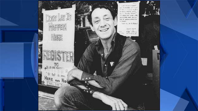 Harvey Milk, as San Francisco Supervisor, sits in front of his camera shop in a 1977 file image (AP)
