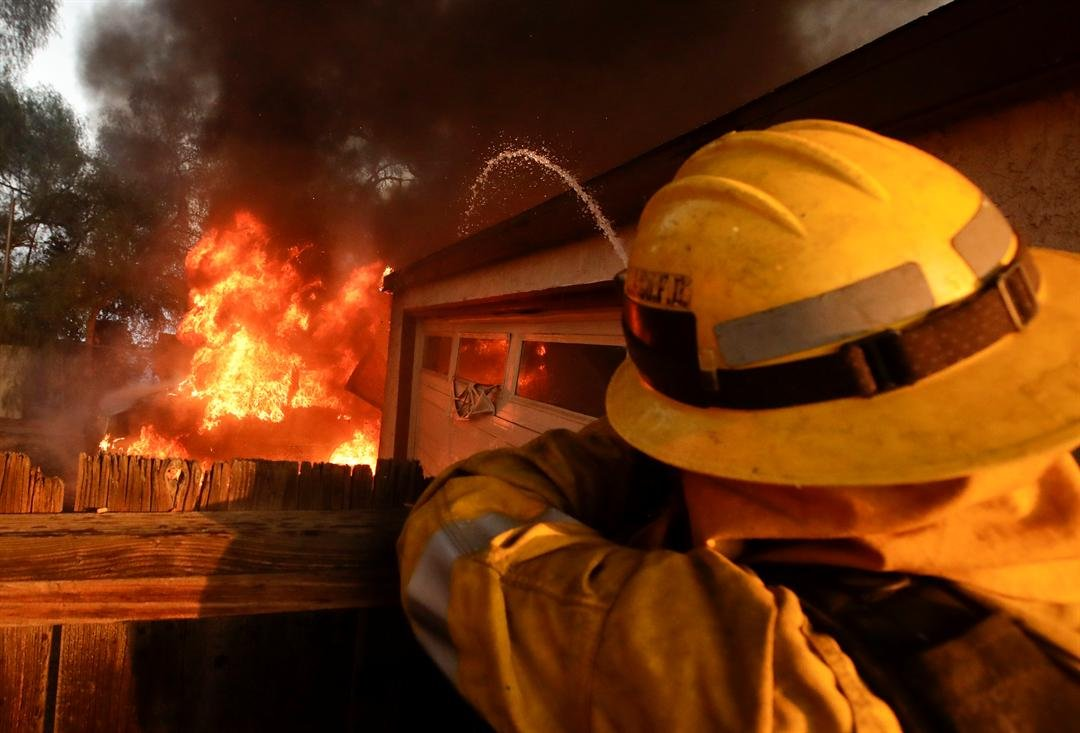 A Los Angeles County firefighter puts water a burning house in a wildfire in the Lake View Terrace area of Los Angeles Tuesday, Dec. 5, 2017. (AP Photo/Chris Carlson)