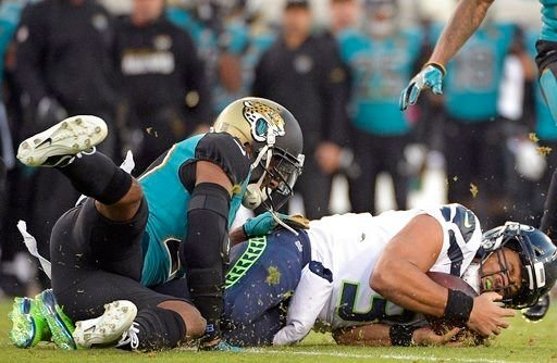 Jacksonville Jaguars cornerback Aaron Colvin, left, stops Seattle Seahawks quarterback Russell Wilson who was diving for yardage during the first half of an NFL football game, Sunday, Dec. 10, 2017, in Jacksonville, Fla. (AP Photo/Phelan M. Ebenhack)