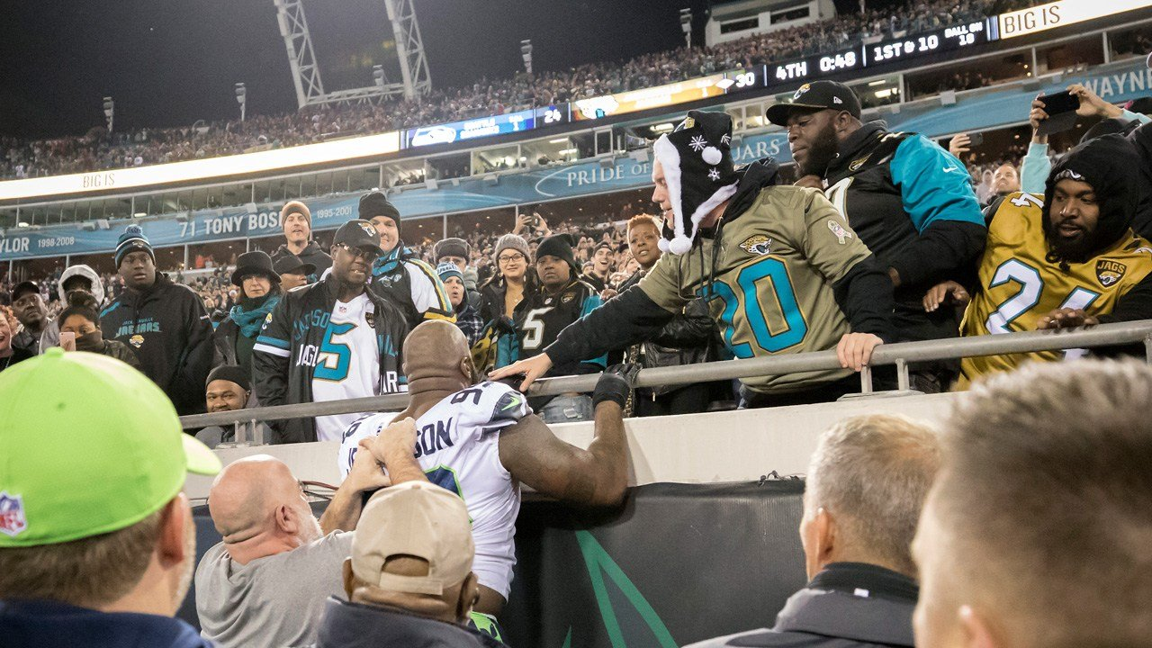 Seahawks DT Quinton Jefferson tries to climb up in the stands after Jaguars fans threw objects at him at the end of the Seattle-Jacksonville game, Sunday, Dec. 10, 2017, in Jacksonville, Fla. Jacksonville won 30-24. (AP Photo/Stephen B. Morton)