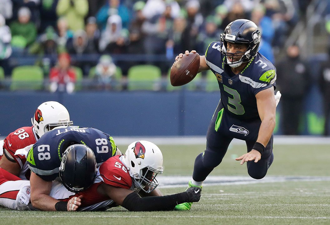 Seattle Seahawks quarterback Russell Wilson is tripped by Arizona Cardinals outside linebacker Chandler Jones in the second half of an NFL football game, Sunday, Dec. 31, 2017, in Seattle. (AP Photo/Elaine Thompson)