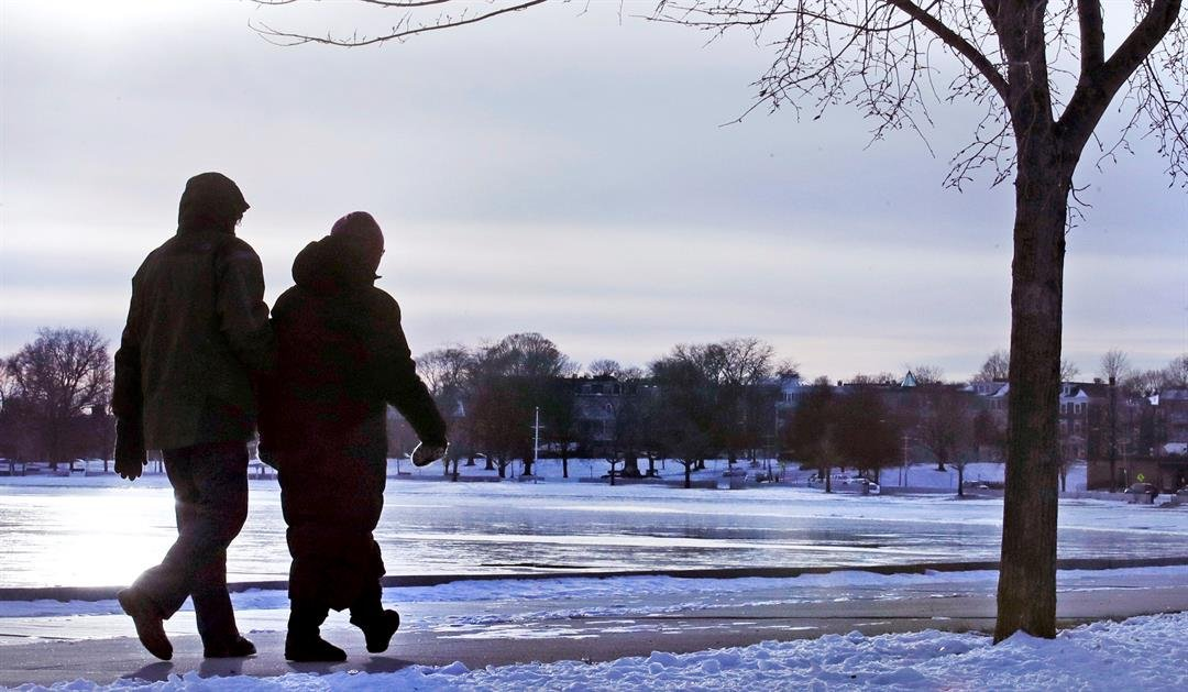 A couple bundled in winter clothing walk along the frozen shore in the South Boston neighborhood of Castle Island, Tuesday, Jan. 2, 2018. (AP image)