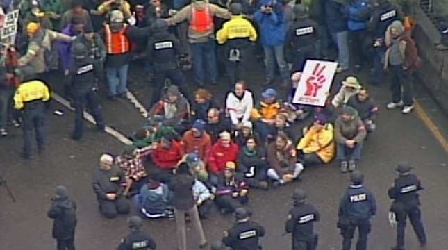 Portland police arrested 25 protesters who sat down on the ramp to the Steel Bridge during the morning rush hour.