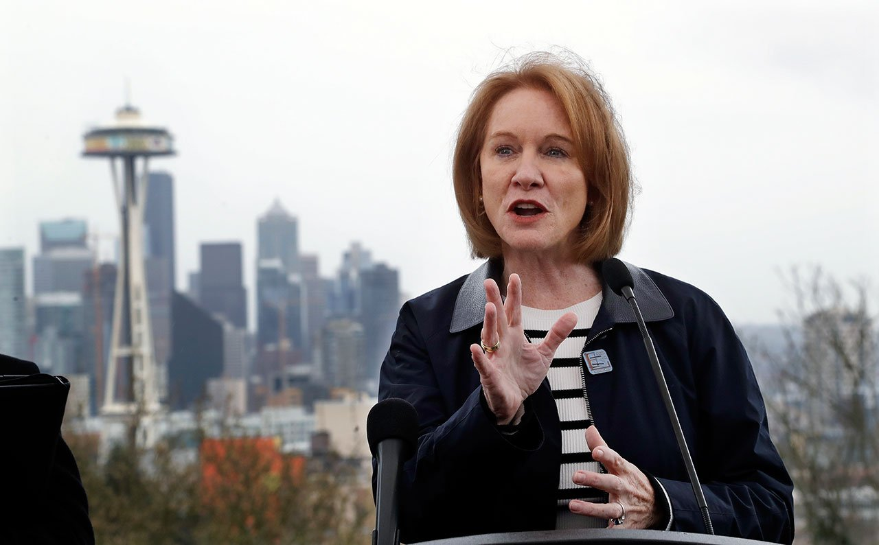 Seattle Mayor Jenny Durkan speaks at a news conference talking about efforts to reduce greenhouse gases in the city as she stands at a viewpoint looking toward downtown Wednesday, April 4, 2018, in Seattle. (AP Photo/Elaine Thompson)