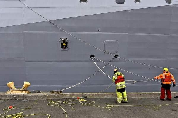 Workers help dock the USS Portland at the Port of Astoria. Photo used with permission from The Daily Astorian/Colin Murphey.