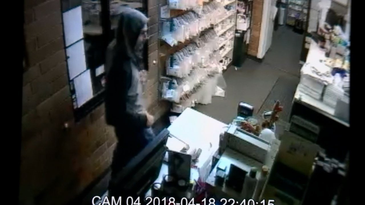 Pill Box security footage shows a suspect enter the store through a window and leave with several items in hand.