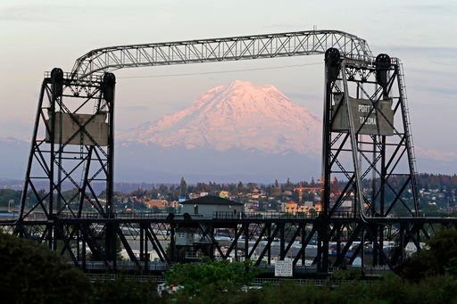 (AP Photo/Ted S. Warren). In this May 7, 2018 photo, Mount Rainier is seen at dusk and framed by the Murray Morgan Bridge in downtown Tacoma, Wash.