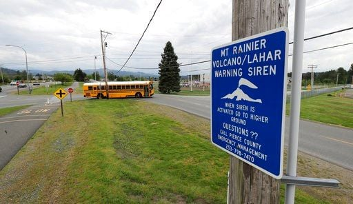 (AP Photo/Ted S. Warren). In this May 8, 2018 photo, a sign under a lahar warning siren is shown as a school bus drives near Orting Middle School in Orting, Wash.