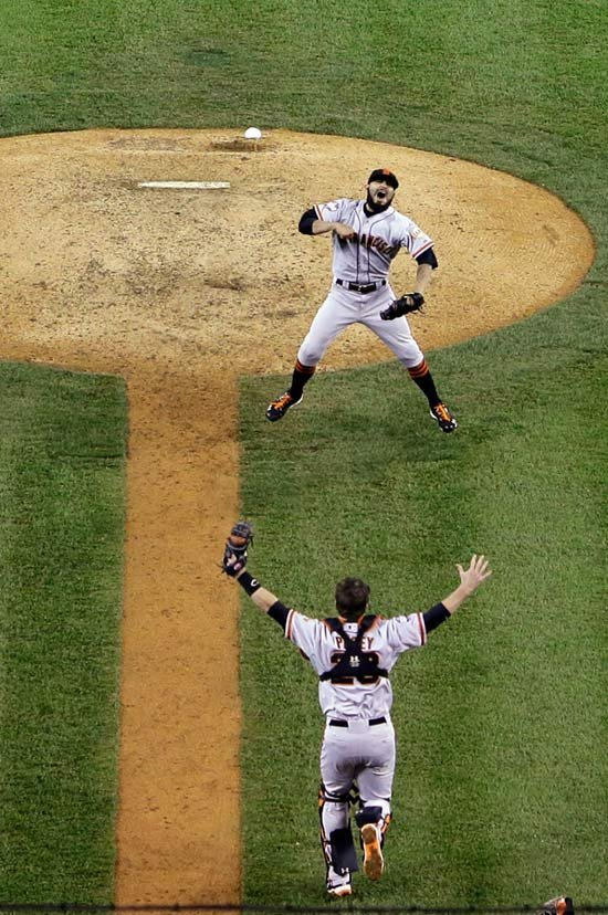 San Francisco Giants relief pitcher Sergio Romo and catcher Buster Posey celebrate after winning the World Series. Both Romo and Posey played for the Salem-Keizer Volcanoes. (AP Photo/Tim Donnelly)