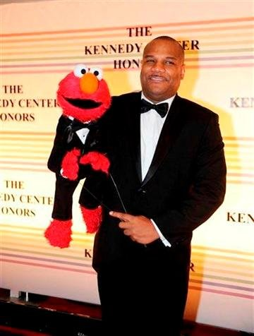 """(AP Photo/Kevin Wolf) This Dec. 4, 2011 file photo shows """"Sesame Street"""" character Elmo and puppeteer Kevin Clash arrive at the Kennedy Center for the Performing Arts for the Kennedy Center Honors gala performance in Washington."""