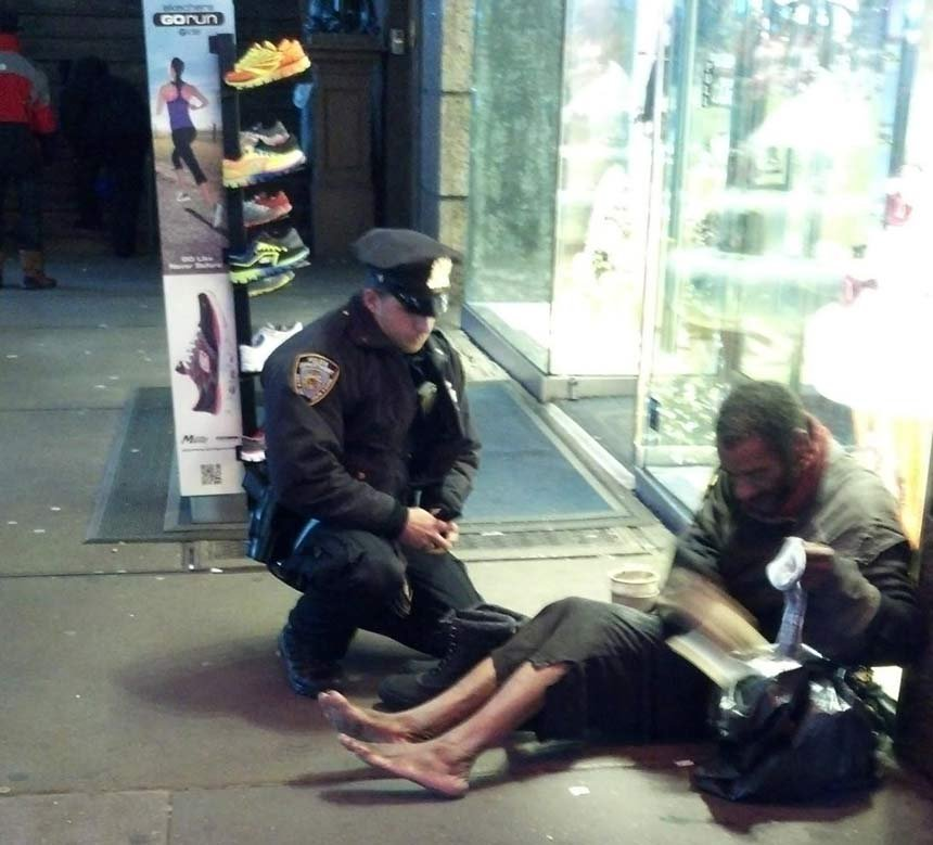 A photo taken by Jennifer Foster shows New York City Police Officer Larry DePrimo presenting a barefoot homeless man in New York's Time Square with boots. Foster was visiting New York with her husband on Nov. 14, when she came across the pair.