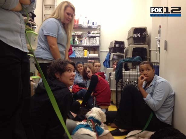 A group huddles in the back room of a pet store at Clackamas Town Center.