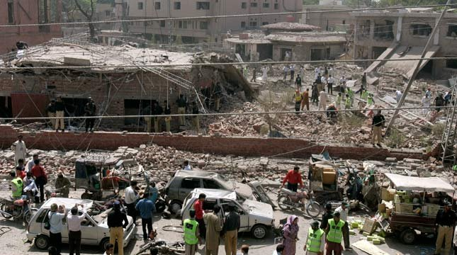 Pakistani security officials and rescue workers gather at the site of suicide car bombing in Lahore, Pakistan on Wednesday, May 27, 2009. (AP Photo/K.M. Chaudary)