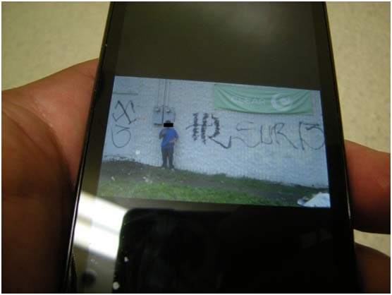 Suspect's phone, with photo posing with the graffiti