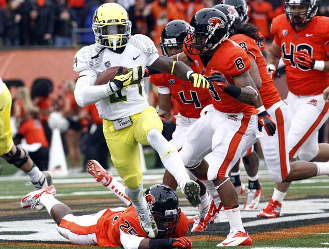 Oregon running back Kenjon Barner (24) heads down field ahead of a pack of Oregon State defenders during the first half of their NCAA college football game in Corvallis, Ore., Saturday, Nov. 24, 2012. (AP Photo/Don Ryan)