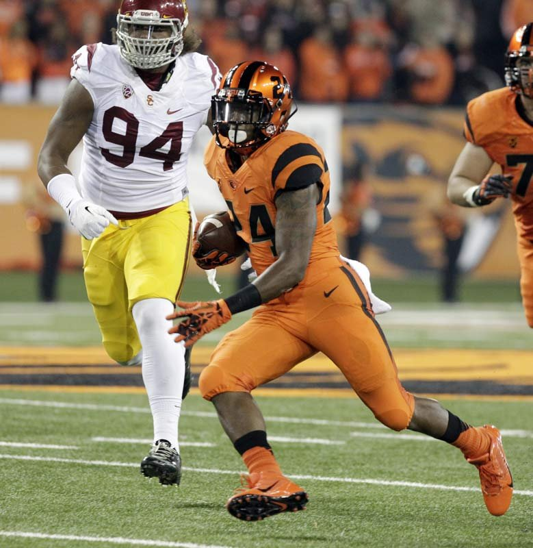 Oregon State running back Storm Woods, right, rushes ahead of Southern California defender Leonard Williams during the first half of an NCAA college football game in Corvallis, Ore., Friday, Nov. 1, 2013. (AP Photo/Don Ryan)
