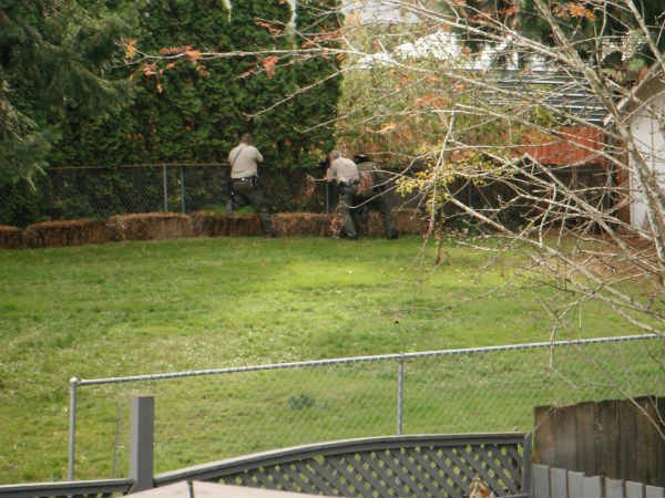 Deputies search the neighborhood in the wake of a house fire and shooting in Oregon City.