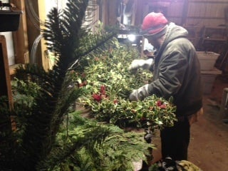 Brian Clark creates a wreath inside the shop at his farm in southwest Portland.