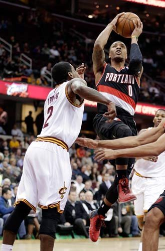 Damian Lillard jumps to the basket against Kyrie Irving in Tuesday's game in Cleveland. (AP Photo/Tony Dejak)