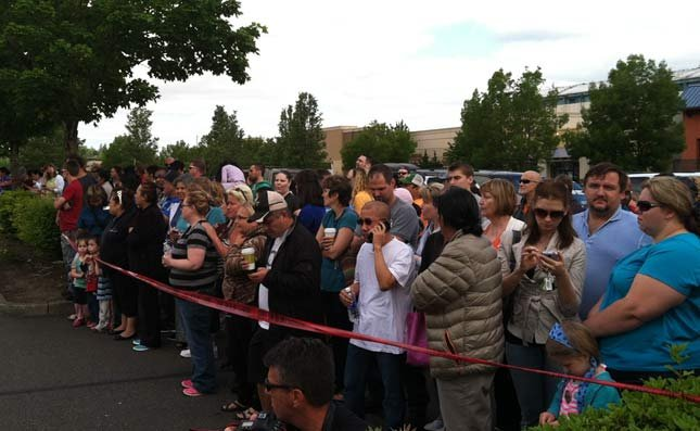 Parents wait at Fred Meyer for students to arrive on buses from Reynolds High School.