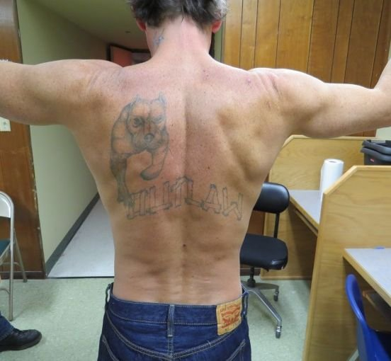 """""""Outlaw"""" and pit bull back tattoo of wanted murder suspect Daniel Martinson. Photo: Oregon State Police."""