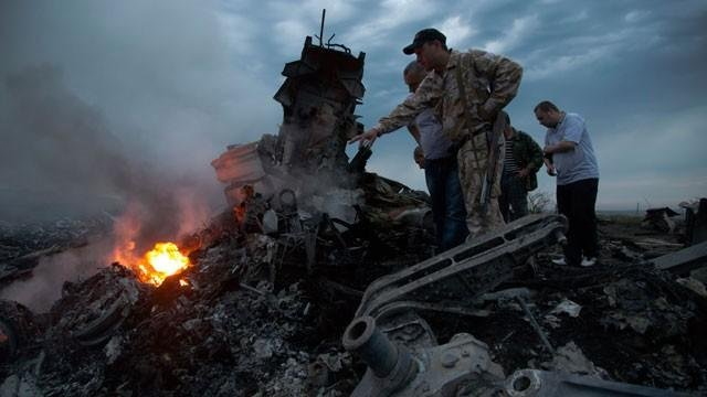 People inspect the crash site of a passenger plane near the village of Grabovo, Ukraine, Thursday, July 17, 2014. Both the government and the pro-Russia separatists fighting in the region denied any responsibility for downing the plane. (AP Photo)