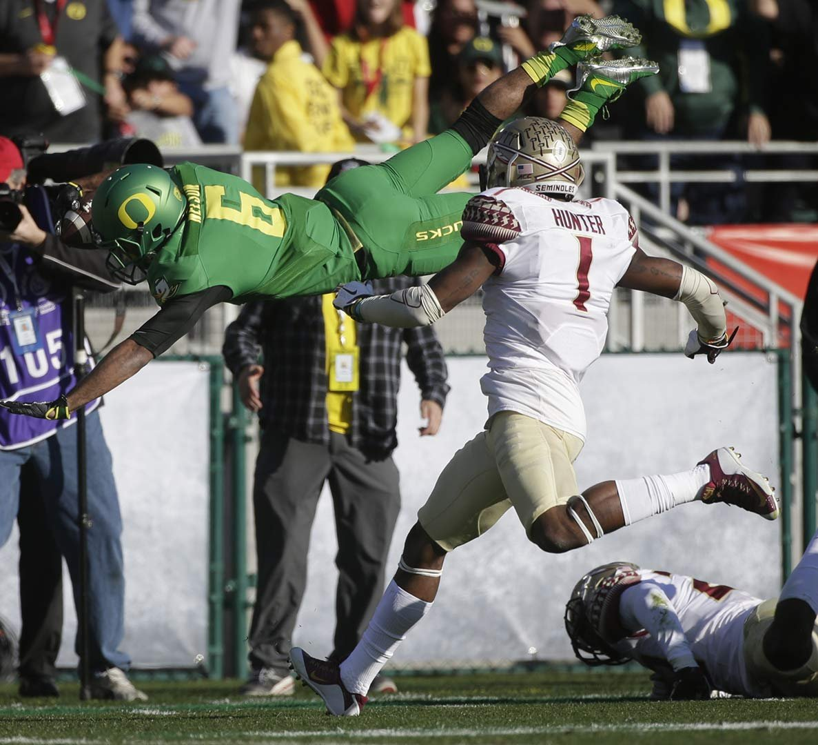Oregon wide receiver Charles Nelson, left, dives over Florida State safety Tyler Hunter during the first half of the Rose Bowl NCAA college football playoff semifinal, Thursday, Jan. 1, 2015 in Pasadena, Calif. (AP Photo/Jae C. Hong)