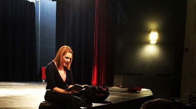 """Photo of Stephanie McCrea from Evergreen High School's drama department Instagram account. The post from four months ago says, """"Director Stephanie McCrea reading from Night by Elie Wiesel, giving the cast some background information on Nazi Germany."""""""