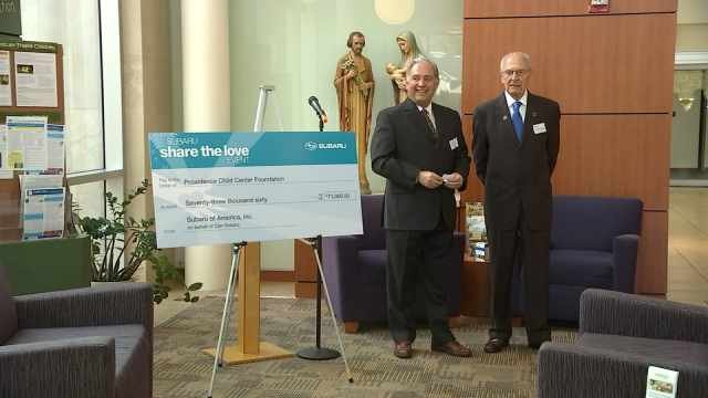 Bill Schonely accepting the check on behalf of Bill's Kids and Providence Child Center.
