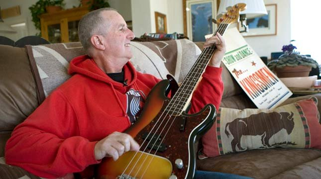 """In this April 16, 2009 photo, Jack Ely, co-founder of The Kingsmen and best known for his 1963 rendition of """"Louie, Louie"""", plays his Fender bass guitar at his small horse ranch in Terre Bonne, Ore. (AP Photo/Don Ryan)"""
