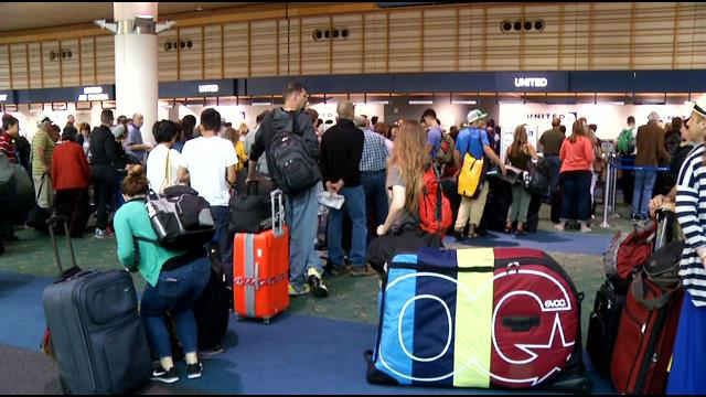 United Airline passengers waiting in line at PDX during technical glitch.