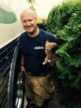 Firefighter Jon Bacon holding Little Flame.