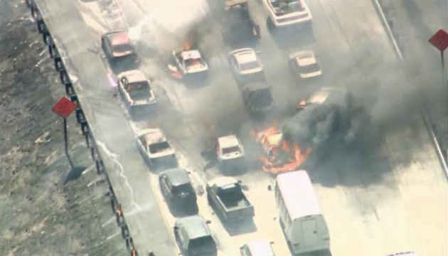 A fast-moving wildfire swept across a freeway Friday in a Southern California mountain pass, torching at least a half-dozen cars and a tractor trailer as motorists abandoned their vehicles and ran to safety. (Source: KABC/CNN)