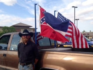Russell Smith with the American flag and the Mississippi state flag.