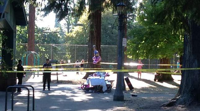 Crime scene tape surrounded a table stacked with presents at Laurelhurst Park as police conducted a shooting investigation.