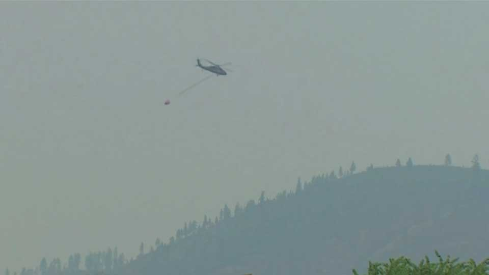 A helicopter drops water on the Chelan Complex of fires in Washington