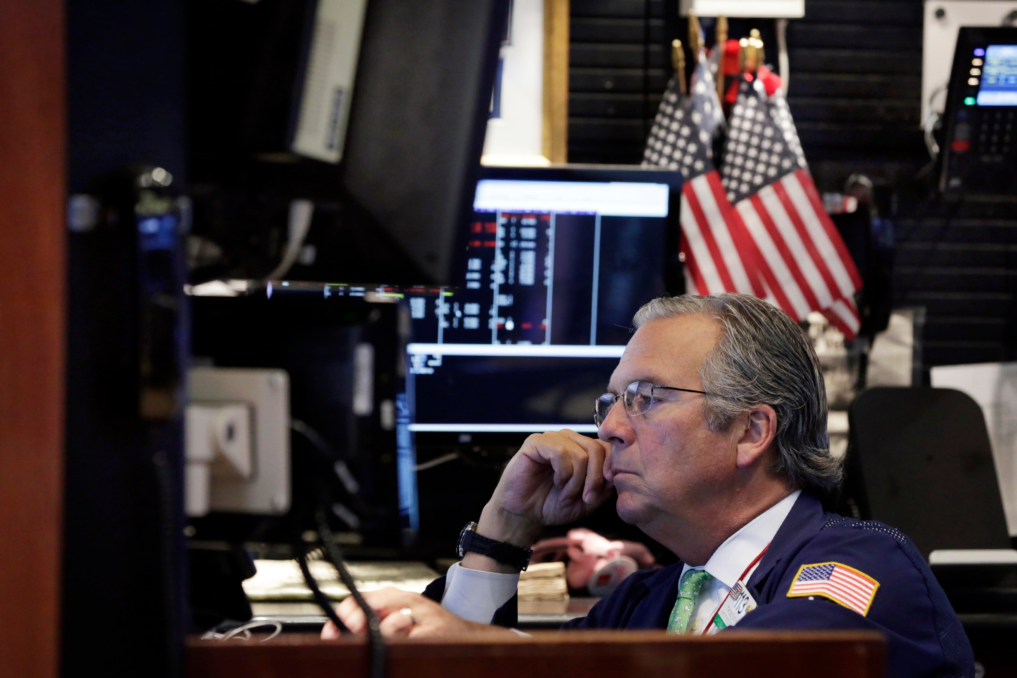 Trader Thomas Kay looks at screens in his booth before the opening bell of the NYSE, Mon, Aug. 24, 2015. World stock markets plunged on Monday after China's main index sank 8.5 percent, its biggest drop since the early days of the global financial crisis.