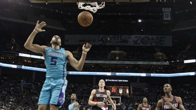 Charlotte Hornets' Nicolas Batum (5) dunks past Portland Trail Blazers' Mason Plumlee (24) and Noah Vonleh (21) in the second half of an NBA basketball game in Charlotte, N.C., Sunday, Nov. 15, 2015. The Hornets won 106-94. (AP Photo/Chuck Burton)