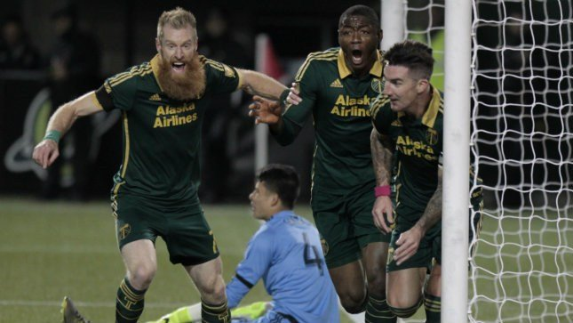 Portland Timbers defender Nat Borchers, forward Fanendo Adi and defender Liam Ridgewell, celebrate Ridgewell's goal during the first leg of the MLS soccer Western Conference championship against FC Dallas, Sunday, Nov. 22, 2015. (AP Photo/Steve Dipaola)