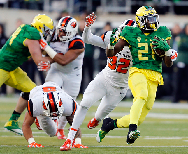 Oregon running back Royce Freeman, right, tries to pull away from Oregon State's Jonathan Willis (32) in the second half of an NCAA college football game, in Eugene Ore., on Friday, Nov. 27, 2015. Oregon won 52-42.
