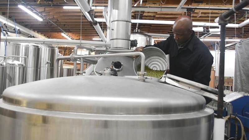 Terry Porter pouring hops into brew at Gilgamesh Brewing (Photo: Gilgamesh Brewing)