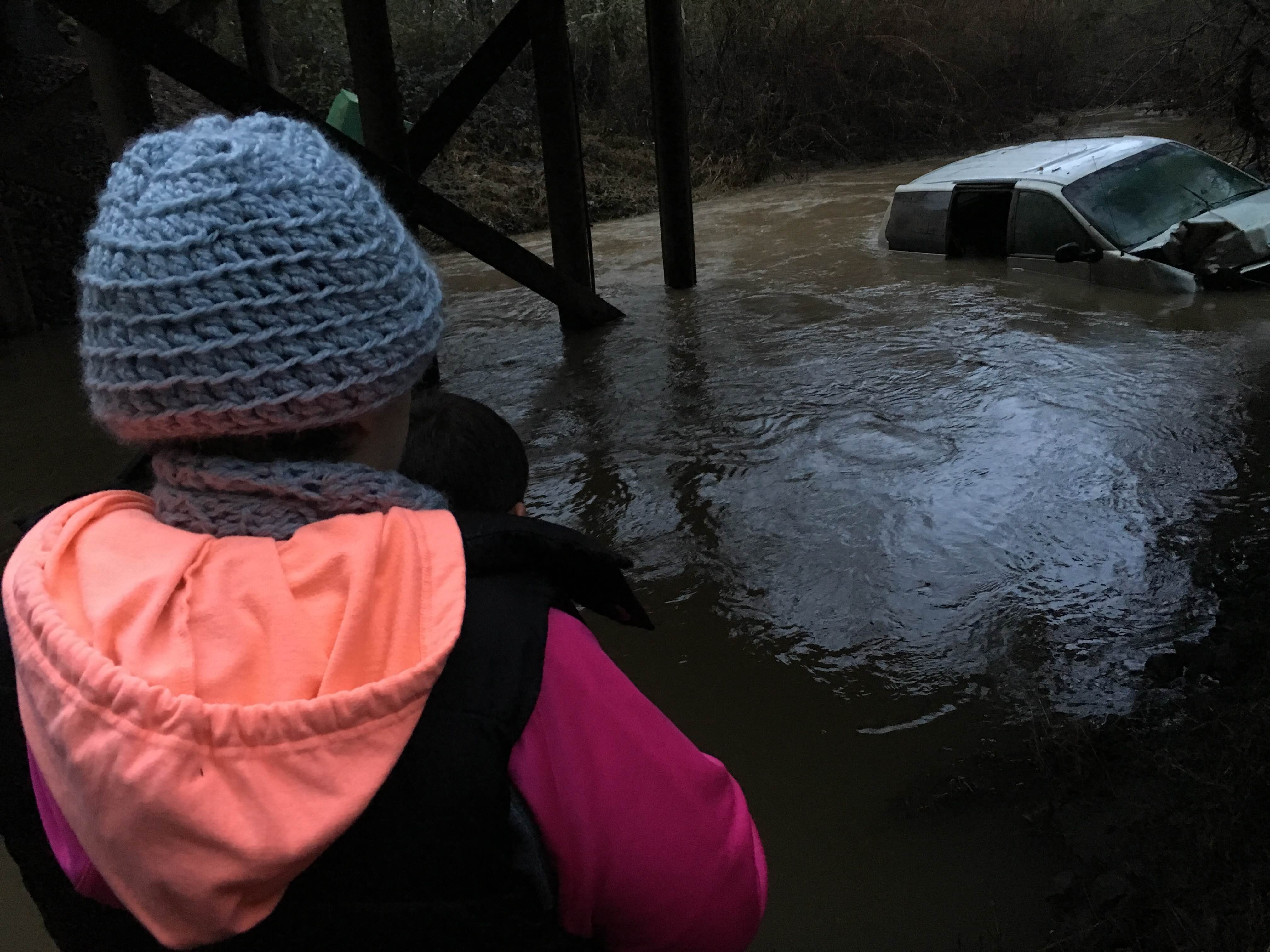Wilder looks at her half submerged van.
