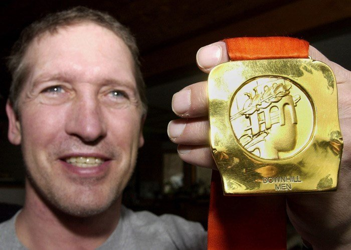 Skier Bill Johnson, who won the 1984 Olympic gold in men's downhill, displays his medal at his family's home in Gresham, Ore., Wednesday, Feb. 6, 2001.
