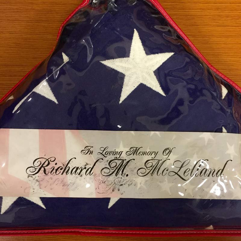 """A memorial flag that says, """"In Loving Memory of Richard M. McLelland,"""" was dropped off at the Maison Readiness Center in Portland in hopes of reuniting it with its rightful family."""