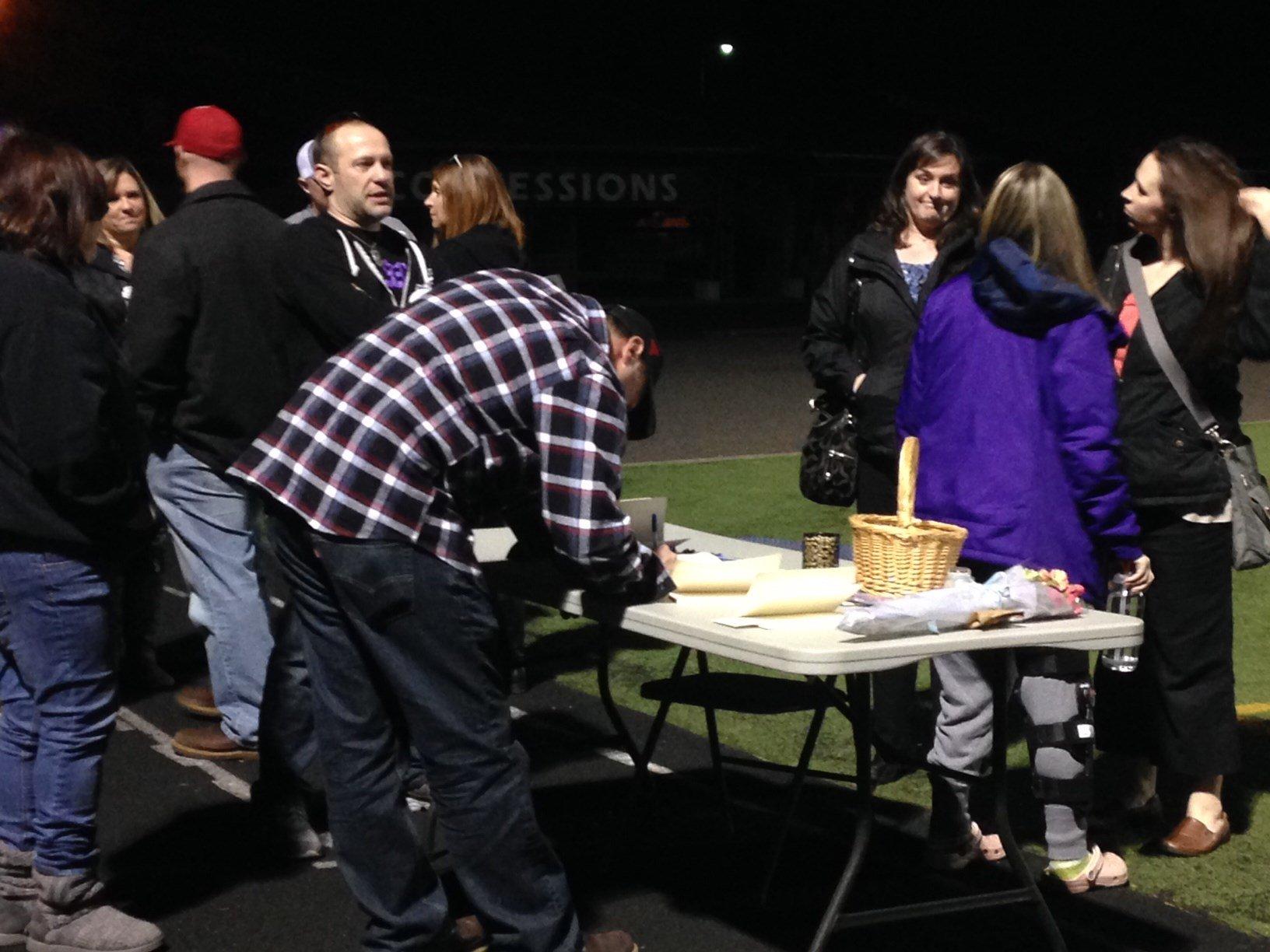 People signing notes at Monday's vigil at Sherwood High School.