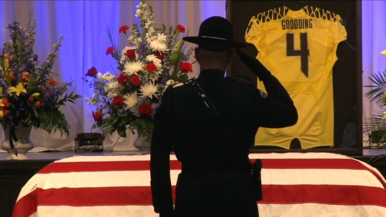 A first responder salutes the remains of Sgt. Jason Goodding at his memorial in Seaside, Oregon. (KPTV)