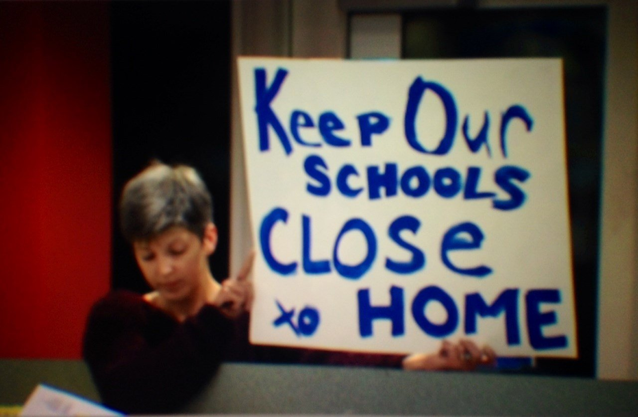 A mother holding a sign at Tuesday's boundary meeting.