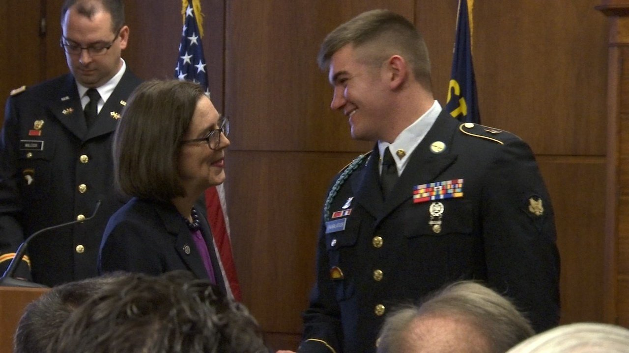 Gov. Kate Brown congratulates Alek Skarlatos after awarding him the Oregon Distinguished Service Award in Salem on Wednesday. (KPTV, Mega Sugianto)