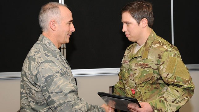 Brig. Gen. Jeffery Silver, Oregon National Guard Air Component Commander, presents Senior Airman Randy Theisen, of the 125th Special Tactics Squadron, with a Bronze Star medal during a ceremony at Portland Air National Guard Base, OR.(US Air Nat. Guard)